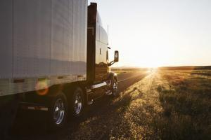 Side view of a trailer and truck on the road at sunset in eastern Washington, USA
